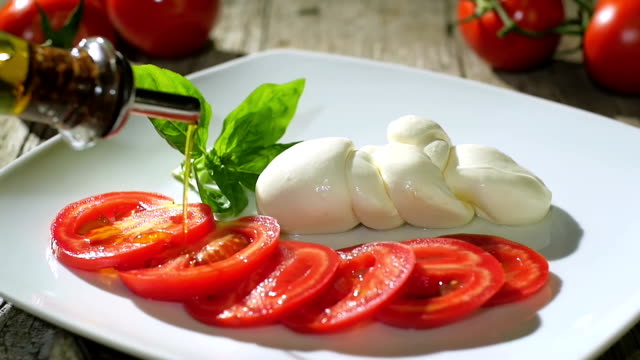 pouring olive oil over caprese salad video