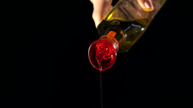 pouring olive oil with the bottle. Slow Motion video