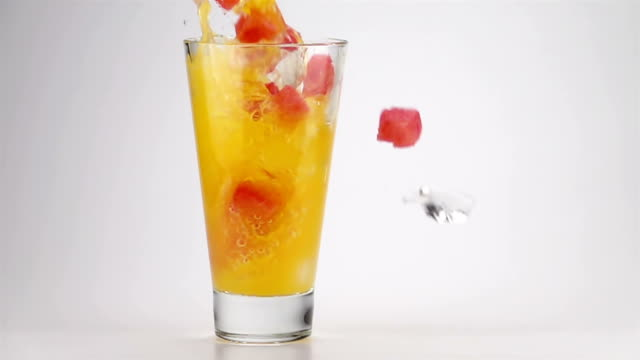 Pouring Orange Soda with the Ice and Watermelon Cubes into a Glass video