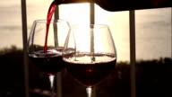 Pouring red wine in to glasses on balcony video