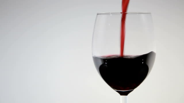 Pouring red wine into a glass.close-up video