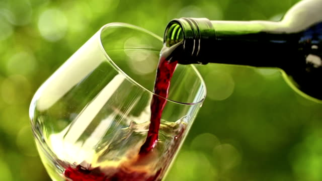 Pouring red wine into a wineglass in slow motion video
