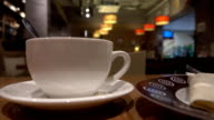 Pouring tea from teapot in the cup in a cafe. FullHD close up shot video
