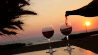 pouring two glasses of wine at the sunset: aperitif, cocktails, red wine, summer video