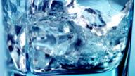 Pouring water into a glass with cubes of ice. video