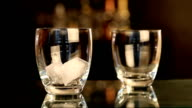 Pouring whiskey and ice in a glass video