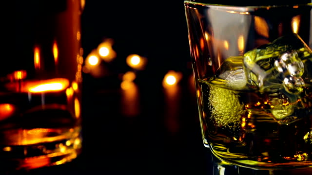pouring whiskey on bar table in front of bottles on warm atmosphere, relax time with whisky video