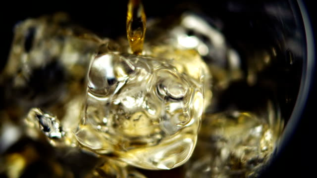 Pouring Whiskey on Ice in glass video