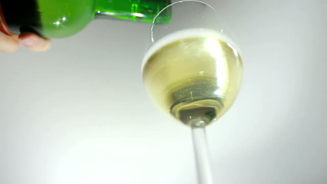 Pouring white wine from the bottle into a glass video