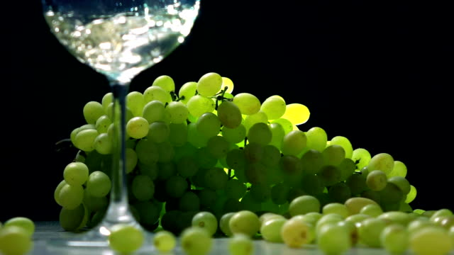 Pouring white wine into glass against the bunch of green grapes. Winemaking concept. Super slow motion shot video