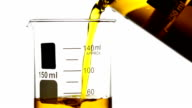 Pouring yellow liquid into Beaker video