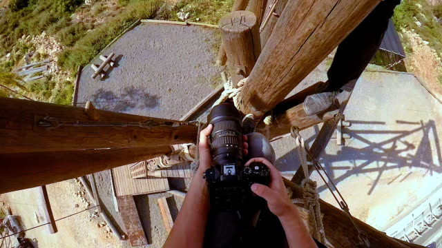 Pov of extreme professional videographer during shooting on climbing tower working under extreme conditions video