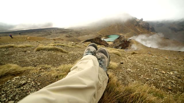 Pov of hiker's legs relaxing by the mountain lake video
