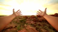 Pov of person stretching arms towards Devil's Marbles at sunrise video