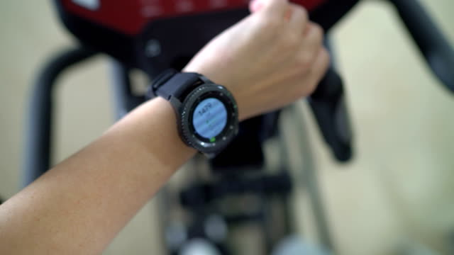 PoV of woman doing cardio on elliptical trainer checking workout on smart watch video