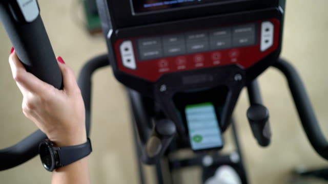 PoV of woman exercising on elliptical trainer with smartphone video