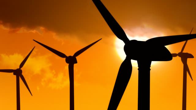 Power Generating Windmills at sunset against orange sky. Loopable video