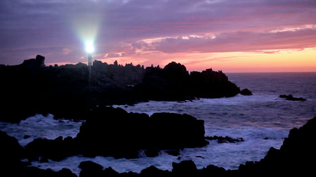 powerful lighthouse and rocky coastline at dusk video