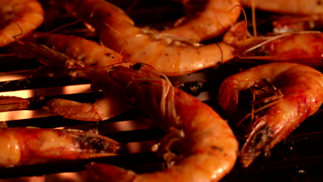 Prawns with spicy seasoning grilling on a barbecue at night video