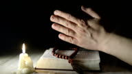 praying hands over a holy book video