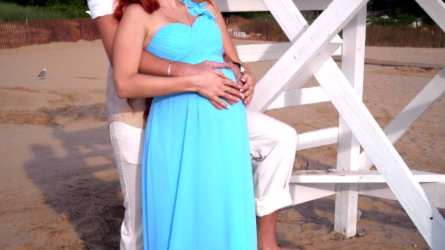 Pregnant couple holding belly. Woman in blue dress holding her belly video