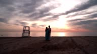 Pregnant couple talking at sunset. Love concept. Romantic couple on sea beach video