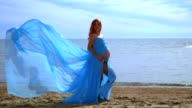 Pregnant model in blue dress flying on wind. Romantic photo session video
