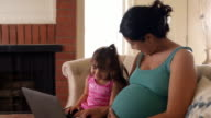 Pregnant Mother and Daughter Laugh Together on Couch video
