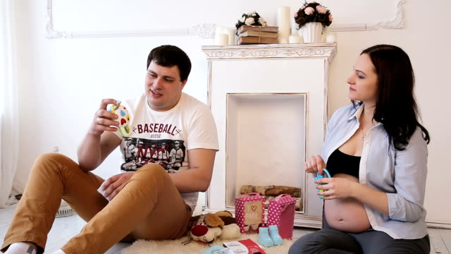 Pregnant woman and her husband and newborn clothing video