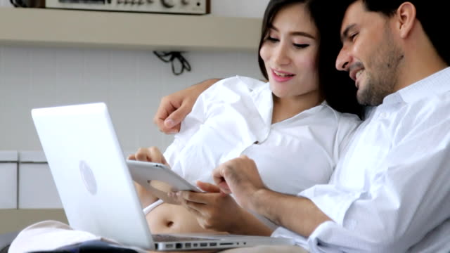 Pregnant woman and husband using laptop at home relaxing on sofa.HD format. video