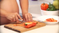 pregnant woman cuts pepper in the kitchen. vegetables for salad video