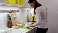 Pregnant woman cutting grape in the kitchen video