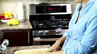 Pregnant woman in her kitchen cutting vegetables. video