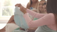 Pregnant woman showing baby clothing to her friends video