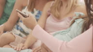 Pregnant woman showing images on cellphone to her friends video