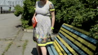 Pregnant woman sitting on a bench video