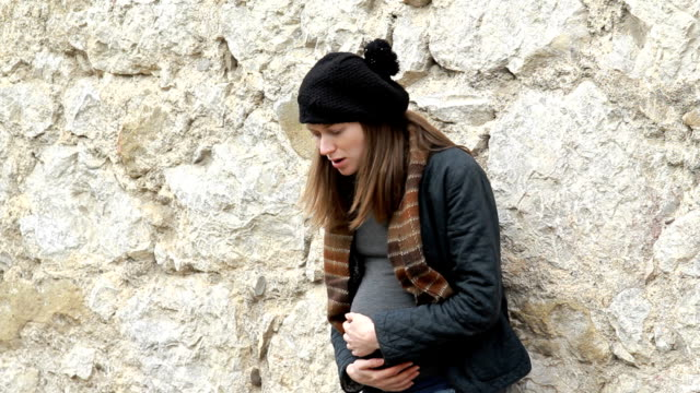 Pregnant woman standing near the city wall video