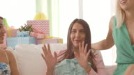 Pregnant woman talking to her friends on baby shower party video