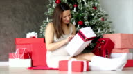 Pregnant woman under Christmas tree holding present gift box video