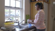Pregnant Woman Washing Dishes In Kitchen Sink video