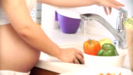 pregnant woman washing peppers in the kitchen. vegetables for salad video