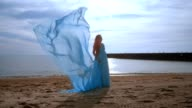Pregnant woman with blue cloth flying on beach. Pregnancy concept video