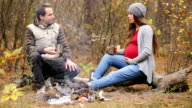 Pregnant woman with her husband resting by the fire video