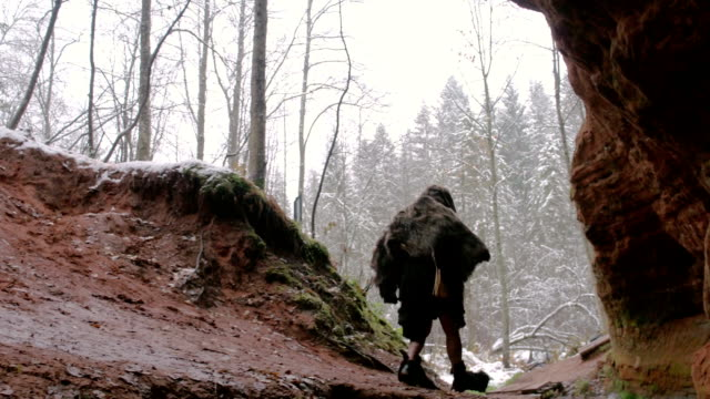 Prehistoric caveman goes outside from his cave on a background of winter forest video