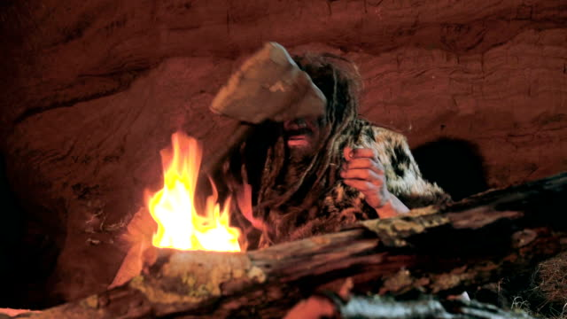 Prehistoric caveman looks at the fire and his spear in his cave video