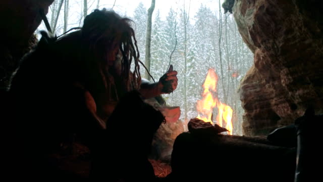 Prehistoric caveman prepares a potion or medicine in his cave on a background of winter forest video