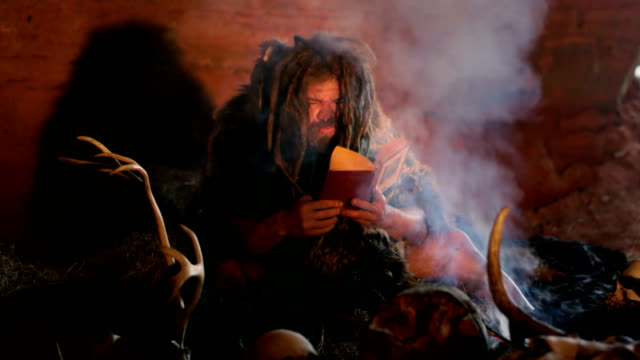 Prehistoric caveman reads book video