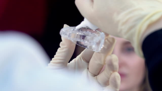 Preparation for teeth whitening for a young girl, puts gel on whitening trays. video