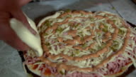 Preparation of homemade pizza on a light kitchen table, close-up shot. video