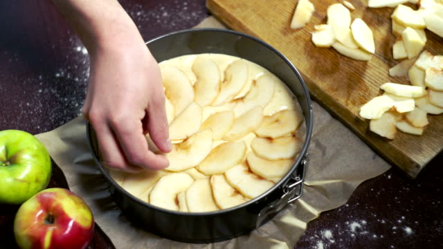 Preparing for baking apple pie. Cook puts apple slices in baking dish video